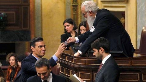 El presidente del Gobierno en funciones, Pedro Sánchez, entrega su voto para la Presidencia del Congreso al presidente de la Mesa de edad, el diputado Agustín Zamarrón.