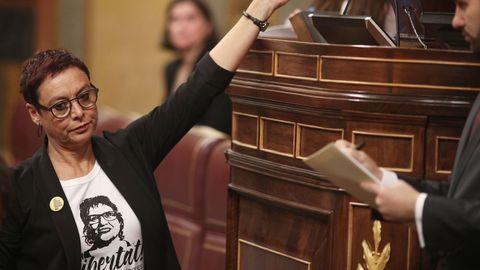 La diputada de ERC, Montserrat Bassa, entrega un papel en el que pone «Llibertat» con un lazo amarillo. Lleva una camiseta el rostro de su hermana, Dolors Bassa, condenada a 12 años de prisión por el Tribunal Supremo por delito de sedición