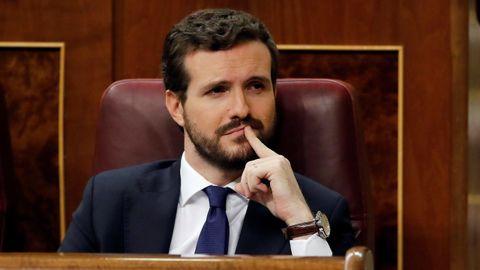 El presidente del PP, Pablo Casado, escucha el discurso de Pedro Sánchez.