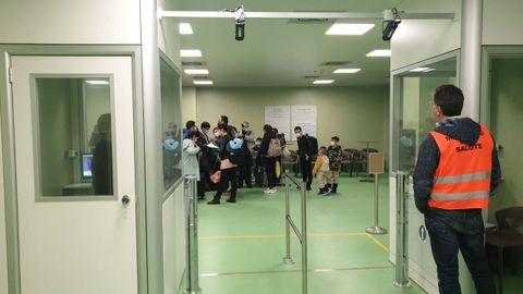 Los pasajeros que llegan al aeropuerto Fiumicino de Roma desde Wuhan en China esperan que el personal médico los revise en busca de signos de coronavirus