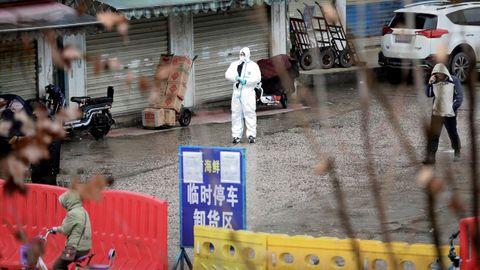 Un trabajador con traje de protección en el mercado cerrado de mariscos en Wuhan, provincia de Hubei, China