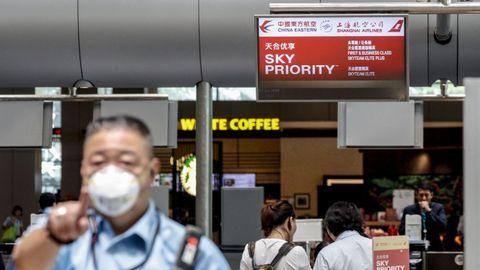 Un guardia de seguridad usa una máscara en el mostrador de facturación del Este de China en el aeropuerto de Changi en Singapur