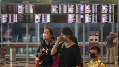 Una madre y sus hijos son vistos usando máscaras mientras caminan por el aeropuerto de Changi en Singapur