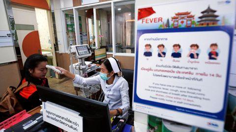 na enfermera mide la temperatura de una paciente al lado de un cartel que alerta del coronavirus, este miércoles en un hospital del Bangkok (Tailandia).