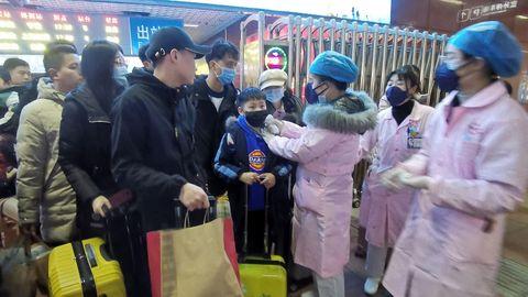 El personal médico verifica la temperatura corporal de los pasajeros cuando llegan a una estación de ferrocarril en la ciudad de Yingtan, provincia de Jiangxi, China