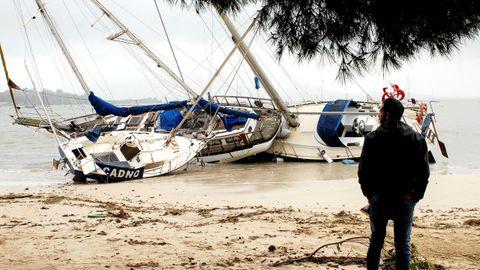 Un hombre mira tres de las embarcaciones varadas en la arena en el Port de Pollença, en Mallorca.
