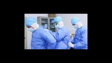 Trabajadores médicos se ayudan para ponerse trajes protectores en el hospital de Zhangzhou