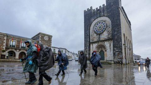 Peregrinos del Camino Francés ante la iglesia de San Xoán de Portomarín