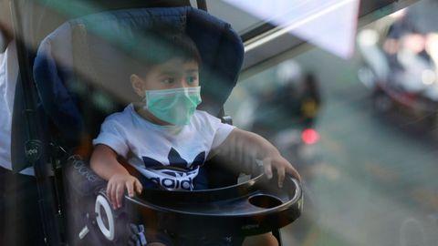 Imagen de un niño con mascarilla en Bangkok