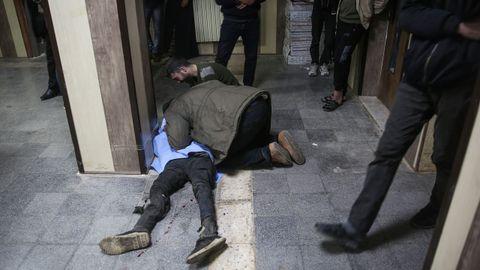 Dos hombres lloran ante el cuerpo de un familiarmuerto en un bombardeo sirio sobre Idlib