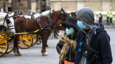 Dos turistas pasean por el casco antiguo de Sevilla con mascarillas