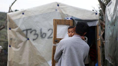 Un hombre sostiene a su hijo  en un campamento improvisado aledaño al campo de Moria