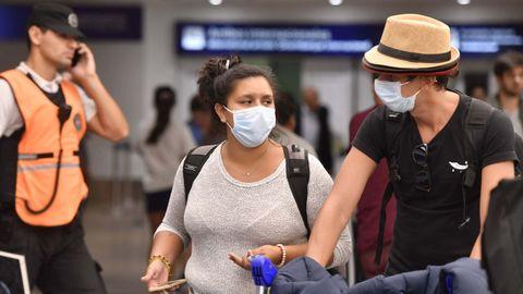 Pasajeros con mascarillas en el aeropuerto de Ezeiza, en Buenos Aires