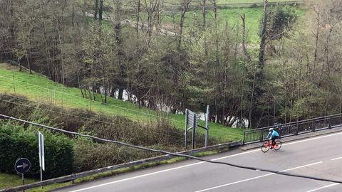 Un ciclista rueda por la entrada a Pola de Siero, por la N-634