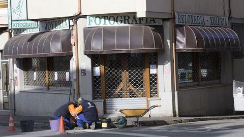 Dos operarios trabajan en una calle vacía de A Fonsagrada