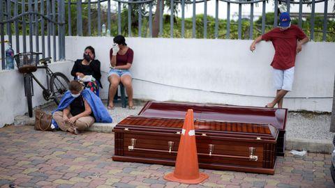 Vecinos de Guayaquil esperan al lado de dos ataúdes colocados en plena calle, cerca de un hospital