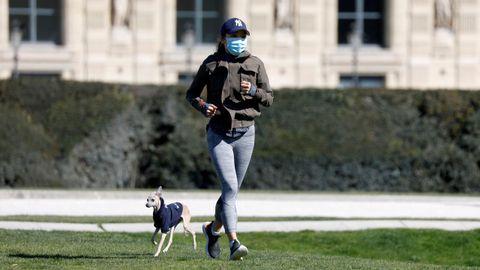 Una corredora parisina, junto a su perro, en los jardines Tuileries