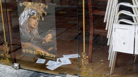 Vista de un cartel que anuncia la Semana Santa en un local comercial en Oviedo durante una nueva jornada marcada por el coronavirus.