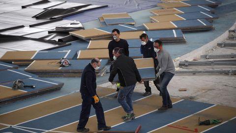 Varios operarios desmontando la pista de atletismo de Sabadell para montar el hospital de campaña