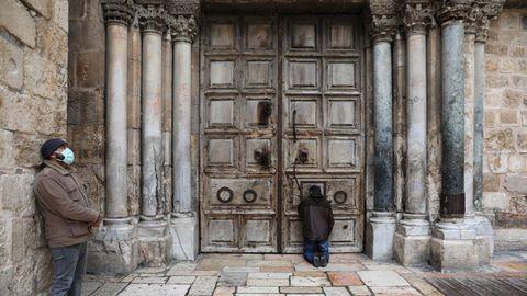 Gente orando a las puertas de la iglesia del Santo Sepulcro, en Jerusalén, donde están cerrados los lugares de culto