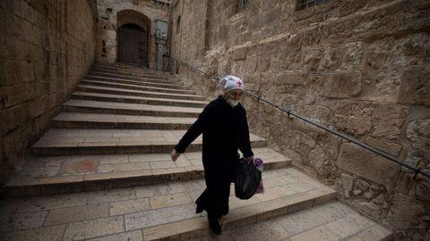 Una monja con mascarilla camina dentro de la iglesia del Santo Sepulcro, en Jerusalén, este Jueves Santo
