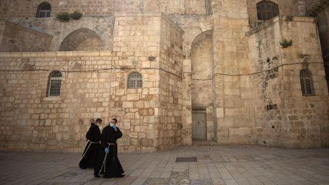 Monjes con mascarillas ante la iglesia del Santo Sepulcro de Jerusalén