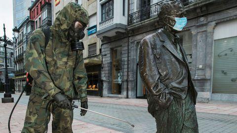 Un soldado desinfecta la estatua de Woody Allen, decorada con una mascarilla, este domingo, en Oviedo