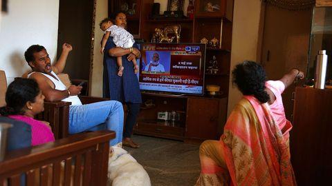 Una familia escucha el discurso televisado del primer ministro indio Narendra Modi en Bangalore, India