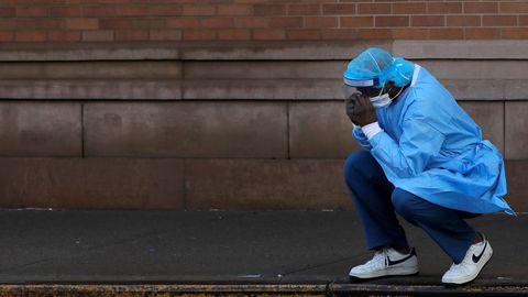 Un trabajador sanitario se toma un descanso, visiblemente afectado, en un hospital de Brooklyn, Nueva York
