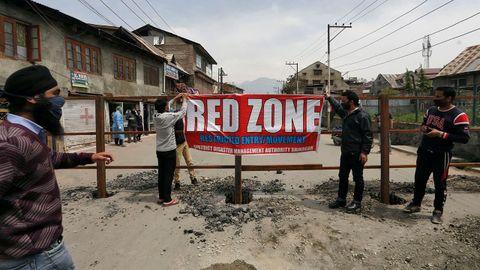 Trabajadores colocan una pancarta en la que se lee  Zona roja  en un barrio infectado por el coronavirus en Srinagar, La India.
