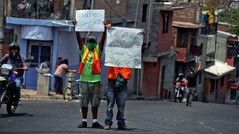 Dos hombres piden dinero y comida mientras sostienen carteles en los que informan su situación de pobreza en Tegucigalpa, Honduras
