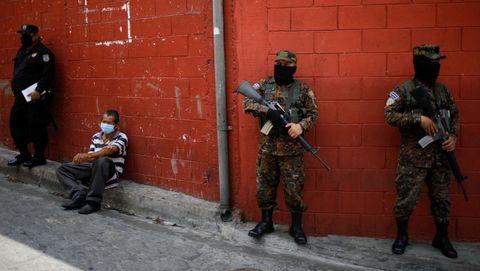 Varios policías custodian a un dentido acusado de violar la cuarentena en San Salvador, El Salvador