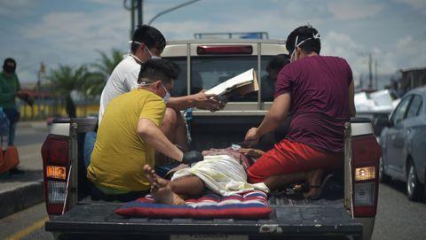 Varios hombres protegidos con mascarillas trasladan a un enfermo en la parte de atrás de una camioneta en Duran, Ecuador