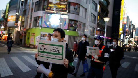 Funcionarios del gobierno metropolitano de Tokio pasean con carteles en los que animan a la población a quedarse en casa