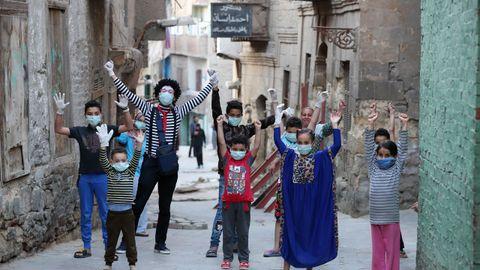 El clown egipcio Ahmed Naser divierte a unos niños, que se protegen con mascarillas, en El Cairo, Egipto