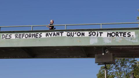 Una mujer hace deporte por un paso elevado en el que se lee una pancarta reivindicativa en París, Francia