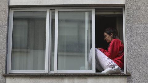 Una joven toma el aire en su piso del Ensanche compostelano
