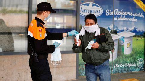 Miembros de Protección Civil de Oviedo reparten mascarillas este martes en la estación de autobuses de Oviedo