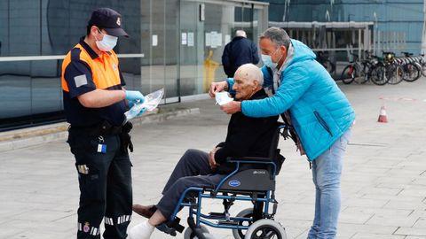 Miembros de Protección Civil de Oviedo reparten mascarillas
