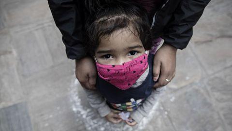 Una niña con su madre espera en Katmandú (Nepal) los artículos de ayuda distribuidos por la Sociedad Musulmana Newa, que ya ayudó a 50 familias de bajos ingresos confinadas. Nepal mantiene desde el 24 de marzo de 2020 las medidas de contención, en un esfuerzo por combatir la propagación del coronavirus