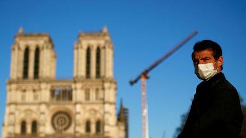 Un hombre con mascarilla escucha la gran campana de la catedral de Notre-Dame de París, que sonó de forma simbólica como señal de la resistencia del edificio un año después del devastador incendio que afectó al monumento
