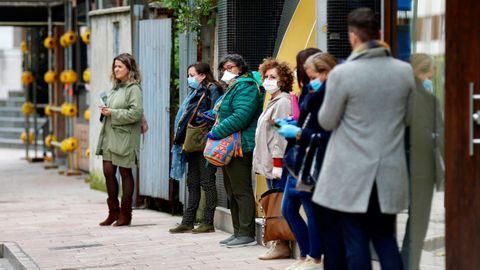 Varias personas esperan en la fila para hacer la compra en un local comercial, este miércoles en el centro de Oviedo.