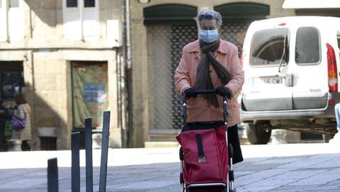Una señora regresa a casa después de hacer la compra, portando mascarilla, en las calles de Santiago