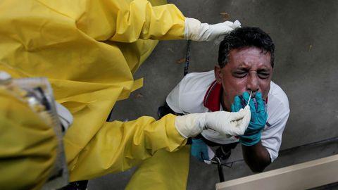 Un hombre reacciona cuando un funcionario de salud usa un hisopo para recolectar una muestra  Sri Lanka