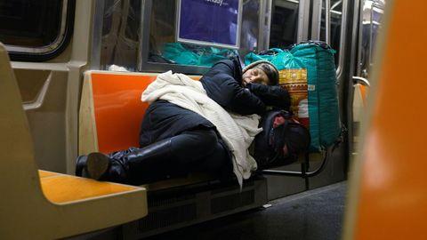 Una mujer duerme en el metro de Nueva York en plena pandemia
