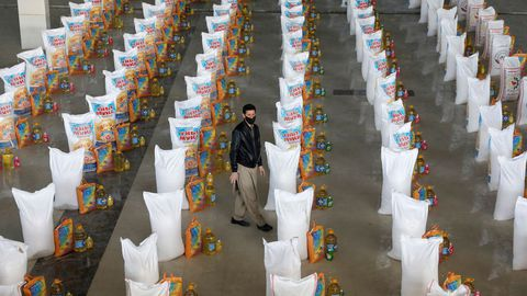 Un afgano, entre los sacos de comida preparados para donar a los más necesitados