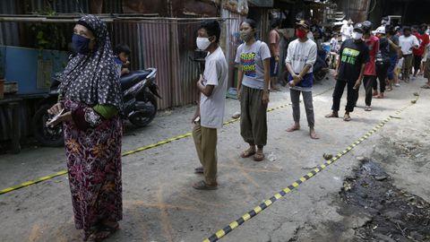 En Yakarta, usuarios de un centro en el que les ofrecen comida, mantienen la distancia social