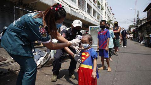 Voluntarios tailandeses controlan la temperatura corporal de una niña durante una distribución gratuita de alimentos
