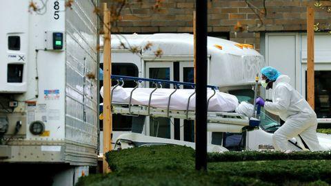 Un profesional sanitario transporta un cadáver en un camión frigorífico en el barrio neoyorquino de Brooklyn