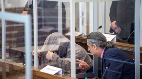 El acusado Eyad Alghareib,  alto cargo del Muhabarat (inteligencia militar),  oculta el rostro en el inicio del juicio